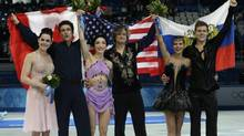 Meryl Davis and Charlie White of the U.S., middle, with Tessa Virtue and Scott Moir of Canada, left, and Elena Ilinykh and Nikita Katsalapov of Russia show off their flags and flowers in Sochi on Monday. (Darron Cummings/AP)