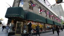 A contractor hangs a sale sign on the window of Stollerys clothing store on Bloor Street in Toronto on Nov. 27, 2013. (Deborah Baic/The Globe and Mail)