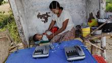 A woman and her child play at a public phone shop in Myanmar, which has fewer phones per capita than any other country and probably the fewest Internet connections. MIT economist and author Daron Acemoglu argues that 'technological change is at the root of economic growth.' (Soe Zeya Tun/Soe Zeya Tun/Reuters)