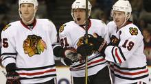 Chicago Blackhawks right wing Marian Hossa, centre, celebrates his second goal of the game with teammates Cam Barker, left, and Jonathan Toews during the third period of Wednesday's win over the San Jose Sharks. (Marcio Jose Sanchez/Marcio Jose Sanchez/AP)