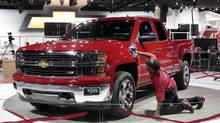Auto show worker Fred Quinn cleans the outside of a General Motor's 2014 Silverado pickup truck at Cobo Center in advance of media preview days of the North American International Auto show in Detroit, Michigan January 12, 2013. The Detroit Three auto makers, which downsized dramatically by closing dozens of factories during the 1990s and 2000s, are almost reaching the point where they need to open new vehicle assembly plants. (REBECCA COOK/REUTERS)