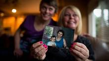 Sonya Paterson, right, and her adopted daughter Carmen Paterson, 28, sit for a photograph at their home in Langley, B.C., on Jan. 28, 2014, while holding a photo of themselves taken in 1990. Paterson co-ordinated hundreds of adoptions in Romania after the Iron Curtain fell in 1989. (Darryl Dyck/The Canadian Press)