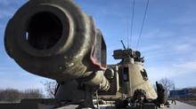 A Ukrainian soldier smiles as he rides in a self-propelled artillery piece near Artemivsk, eastern Ukraine, on Monday. (Evgeniy Maloletka/The Associated Press)