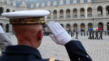 The flag-draped coffin of French lieutenant Damien Boiteux, killed during the French intervention in Mali, is carried by pallbearers into the courtyard of the Invalides in Paris, Jan. 15, 2013. (POOL/Reuters)
