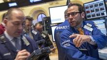 Specialist trader Michael Pistillo, Jr. gives out a price for a trade on the floor of the New York Stock Exchange. Investors seem to be less concerned about slowing monetary stimulus and increasingly confident about the U.S. economy, despite the absence of supporting economic evidence. (BRENDAN McDERMID/REUTERS)