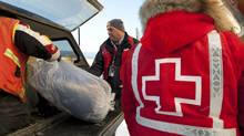 Red Cross workers load sleeping bags into the back of a pick up truck after a shipment of winter supplies arrived by plane the remote Norther Ontario native reserve of Attawapiskat on Nov. 29, 2011. (Adrian Wyld/Adrian Wyld/The Canadian Press)