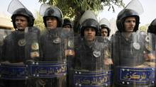 Riot police stand with their shields as members of the Muslim Brotherhood and supporters of ousted Egyptian President Mohamed Mursi protest in front of Egypt's Constitutional Court during the swearing in ceremony of Adli Mansour as the nation's interim president in Cairo July 4, 2013. (AMR ABDALLAH DALSH/REUTERS)
