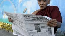 A monk reading a newspaper in Rangoon, Myanmar. (Khin Maung Win/AP)