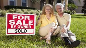 <p>Happy, smiling man and woman senior couple sitting on the grass outside their home ith For Sale Sold by owner sign.</p>
