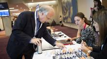 Conference organizer George Przybylowski, left, vice president at Informa Canada, speaks with his organizing team at the RealLeasing conference for real estate in Toronto Sept. 7, 2014. (Darren Calabrese For The Globe and Mail)