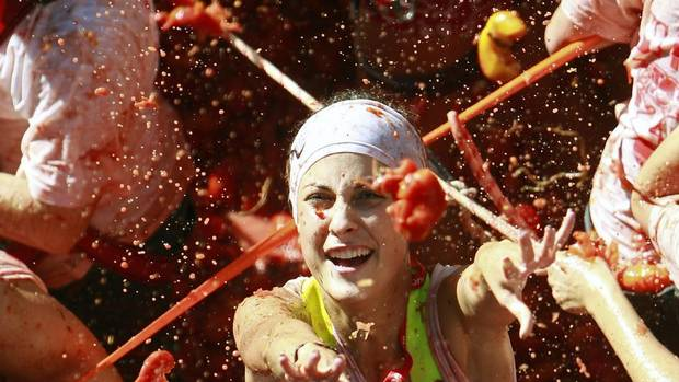 "Revellers throw tomatoes during the annual ""tomatina"" tomato fight fiesta in the village of Bunol, near Valencia, Spain, Wednesday, Aug. 29, 2012. (ALBERTO SAIZ/AP)"