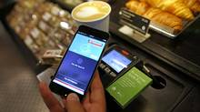A customer uses an iPhone to pay via the Apple Pay system. The service's Canadian launch revealed a rift between Apple and the big banks. (Chris Ratcliffe/Bloomberg)