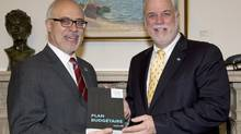 Quebec Premier Philippe Couillard, right, is handed a copy of the provincial budget by Finance Minister Carlos Leitao, Wednesday, June 4, 2014 at his office in Quebec City. (Jacques Boissinot/THE CANADIAN PRESS)