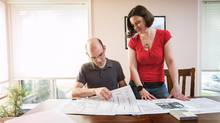 Anthony Jones and Meredith Greenfield look over plans to tear down and rebuild their house. (JENNIFER ROBERTS/THE GLOBE AND MAIL)
