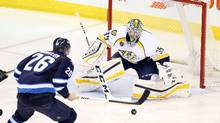 Winnipeg Jets right wing Blake Wheeler (26) looks for a loose puck in front of Nashville Predators goalie Pekka Rinne (35) during the second period at MTS Centre in Winnipeg on Thursday, Jan. 21, 2016. (Bruce Fedyck/USA Today Sports)