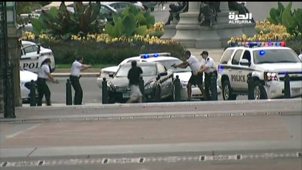 U.S.Capitol Police surround a car with their guns drawn at the corner of Pennsylvania Avenue and 1st Street in this framegrab from Alhurra TV video taken just before a shooting in Washington. (REUTERS/Alhurra/Handout)