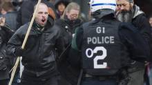 A protester clashes with police during an anti police brutality demonstration in Montreal Saturday, March 15, 2014. (Graham Hughes/THE CANADIAN PRESS)