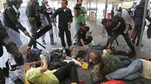 Police detain anti-government protesters after a scuffle near the government house in Bangkok November 24, 2012. Thousands of protesters gathered near parliament in capital Bangkok on Saturday, demanding the ouster of Prime Minister Yingluck Shinawatra. (STRINGER/REUTERS)