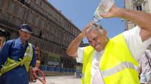 Miloud Belhachemi, right, a construction worker who is building a tramway, pours a bottle of water on his head as temperatures soar to 36C (96.8F), in Marseille southern France, Thursday, July 27, 2006. (CLAUDE PARIS/AP)