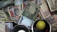 In this photo taken on Nov. 17, 2010, Indian rupee notes lie inside the cash counter of a retail shop in Mumbai. India is especially keen to crack down on tax avoidance on foreign investment via Mauritius. (Rajanish Kakade/AP)