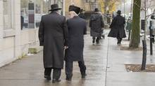 Hasidic Jews walk along Bernard Street in Outremont Wednesday, November 16, 2016 in Montreal. Citizens will vote in a referendum on whether to overturn a bylaw banning places of worship on Bernard Avenue, a busy and colourful street in the borough of Outremont. (Ryan Remiorz/THE CANADIAN PRESS)