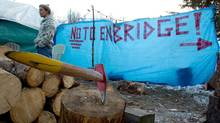Charles Heit, a Gitxsan First Nation member opposed to the $5.5-billion Enbridge oil pipeline from Alberta to the British Columbia port of Kitimat warms himself beside a fire at a camp outside the Gitxsan Treaty Office in Hazelton, B.C., on Thursday January 12, 2012. (DARRYL DYCK/THE CANADIAN PRESS)