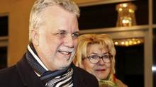 Philippe Couillard arrives at his election rally headquarters with his wife Suzanne Pilot on Monday. (MATHIEU BELANGER/REUTERS)