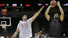 New Mexico State's Sim Bhullar, right, takes a shot as his brother, Tanveer Bhullar, defends during practice for an NCAA college basketball tournament game in Spokane, Wash., Wednesday, March 19, 2014. (Associated Press)