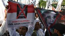 Muslim men hold up banners during a rally against U.S. pop singer Lady Gaga on Friday, May 25, 2012 in Jakarta, Indonesia. (Dita Alangkara/THE ASSOICATED PRESS)