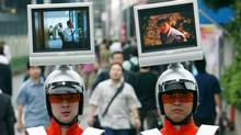 "Japanese advertisement company employees wear ""TV helmets"" to display commercials, as they walk through a street in downtown Tokyo, July 9, 2003. (TOSHIYUKI AIZAWA)"