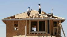 Workers build a house for developer KB Home in Gilbert, Ariz. (JOSHUA LOTT/REUTERS)