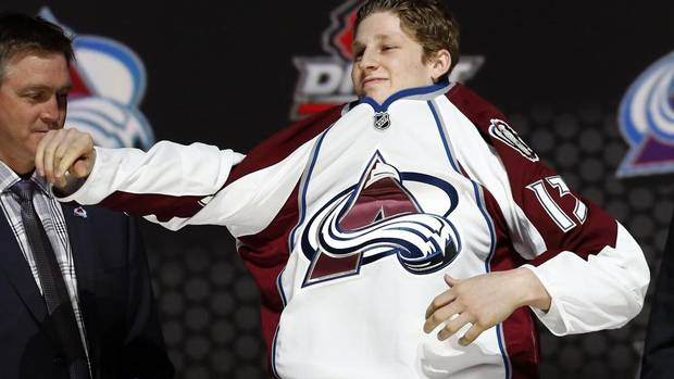 Nathan Mackinnon (R) puts on a Colorado Avalanche jersey after he was selected by the Avalanche as the first overall pick in the 2013 National Hockey league (NHL) draft in Newark, New Jersey, June 30, 2013. (BRENDAN MCDERMID/REUTERS)