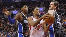 Toronto Raptors' DeMar DeRozan goes to the basket against Elfrid Payton, left, and Mario Hezonja, right, of the Orlando Magic during the first half of NBA basketball action in Toronto, Sunday March 20, 2016. (Mark Blinch/THE CANADIAN PRESS)