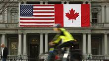 A cyclist passes U.S. and Canadian flags placed side-by-side on the Eisenhower Executive Office Building next to the White House in Washington March 8, 2016. (KEVIN LAMARQUE/REUTERS)