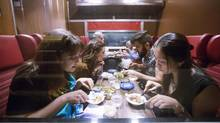 People dine in a reconstructed train car in the basement of a suburban home that is part of Luminato Festival's The Lost Train. (Michelle Siu for The Globe and Mail)