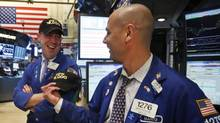 Traders Jarrett Johnson (R) and Mario Picone share a laugh after the Dow Jones Industrial average surpassed 15,000 during trading day on the floor at the New York Stock Exchange, May 3, 2013. (BRENDAN MCDERMID/REUTERS)