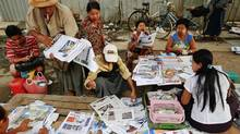 People buy and sell newspapers in central Yangon April 3, 2013. Security has been tightened in parts of Myanmar's biggest city and former capital Yangon after a fire killed 13 boys in a dormitory of an Islamic school on Tuesday. (DAMIR SAGOLJ/REUTERS)