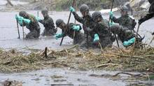 Japan Self-Defence Force soldiers search for missing people at an area hit by landslides caused by heavy rains in Aso, Kumamoto prefecture, in this photo taken by Kyodo on July 14, 2012. (KYODO/REUTERS)