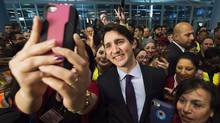 Canadian Prime Minister Justin Trudeau poses for selfies with workers before he greets refugees from Syria at Pearson International airport, in Toronto, on Thursday, Dec. 10, 2015. (Nathan Denette/THE CANADIAN PRESS)