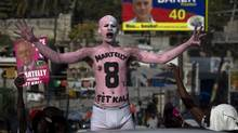 In this Nov. 25, 2010 file photo, a supporter of presidential candidate Michel Martelly, with his body painted, demonstrates during a campaign rally in Port-au-Prince, Haiti. (Ramon Espinosa/AP Photo/Ramon Espinosa)