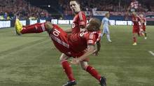 Toronto FC's Robert Earnshaw (foreground) celebrates scoring his team's opening goal against Sporting Kansas City with a backflip as Hogan Ephraim looks on during first half MLS action in Toronto on Saturday March 9, 2013. (Chris Young/THE CANADIAN PRESS)