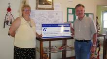 Tory MP Gerald Keddy hands over a government cheque bearing the Conservative Party of Canada logo on July 16, 2009 in LaHave, N.S.