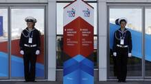 Sailors stand near temporary signs for the G20 summit in St. Petersburg on Sept. 4, 2013. (ALEXANDER DEMIANCHUK/REUTERS)