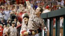 Cincinnati Reds' Scooter Gennett, center, is lifted up by Eugenio Suarez as he celebrates in the dugout during the eighth inning of a baseball game against the St. Louis Cardinals, Tuesday, June 6, 2017, in Cincinnati. (John Minchillo/AP)