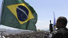 A police officer stands next to the Brazilian national flag atop the Alemao hill in Rio de Janeiro, Nov. 28, 2010. (Sergio Moraes/REUTERS)