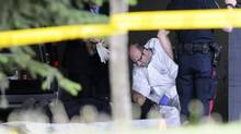 Police forensic investigators examine a dead body at the scene of an armoured car robbery in which at least three were killed at the University of Alberta in Edmonton June 15, 2012. (DAN RIEDLHUBER/REUTERS)