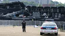 A police officer watches over the Ottawa Bluesfest's collapsed main stage in Ottawa, Monday July 18, 2011. (Adrian Wyld/THE CANADIAN PRESS/Adrian Wyld/THE CANADIAN PRESS)