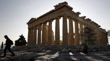 A tourist walks in front of the temple of the Parthenon at the Acropolis in Athens on Monday. (YIORGOS KARAHALIS/YIORGOS KARAHALIS/REUTERS)