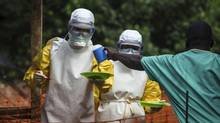Medical staff working with Médecins sans frontières (Doctors Without Borders) prepare to bring food to patients kept in an isolation area at the MSF Ebola treatment centre in Kailahun, Sierra Leone, on July 20, 2014. (TOMMY TRENCHARD/REUTERS)