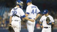 Toronto Blue Jays catcher Josh Thole goes out to talk to pitcher Casey Janssen with Jays third baseman Steve Tolleson after Janssen gave up three runs and the lead to the Detroit Tigers in the ninth inning of their AL baseball game in Toronto Friday August 8, 2014. (Fred Thornhill/THE CANADIAN PRESS)